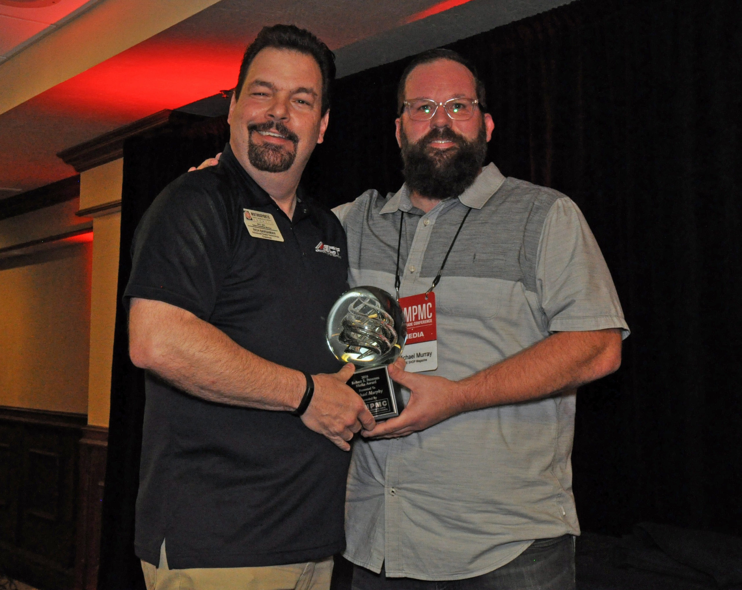 Michael Murray (right), associate publisher of THE SHOP magazine, accepts the Robert E. Pertersen award trophy from MPMC Chair R