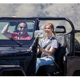 A young woman enjoys driving a classic Jeep at the Hagerty Driving Experience event on May 13 in Golden, Colorado