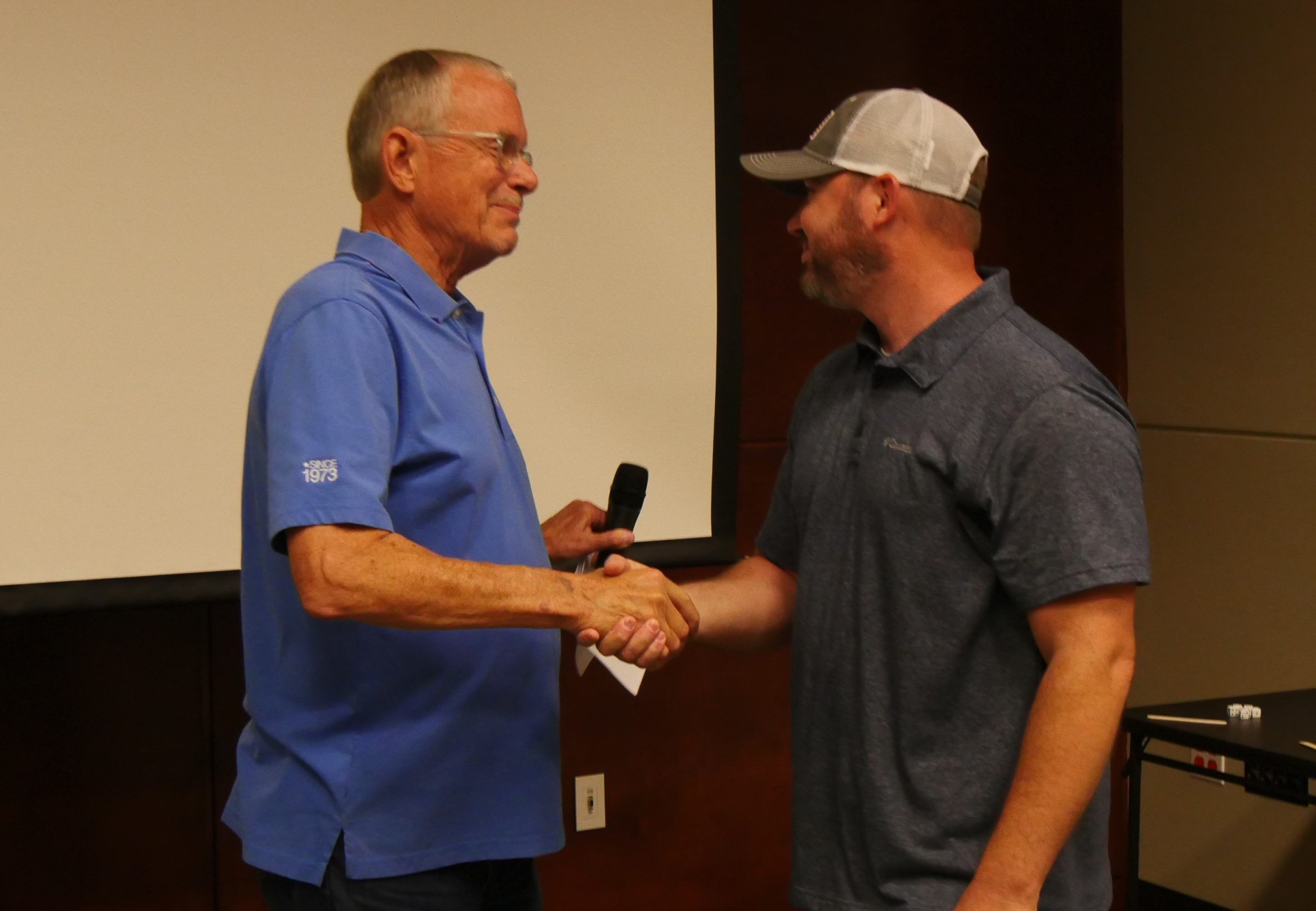 Steve Irby, founder of Stillwater Designs, congratulates Trevis Rakey for his 25-year anniversary with the company.