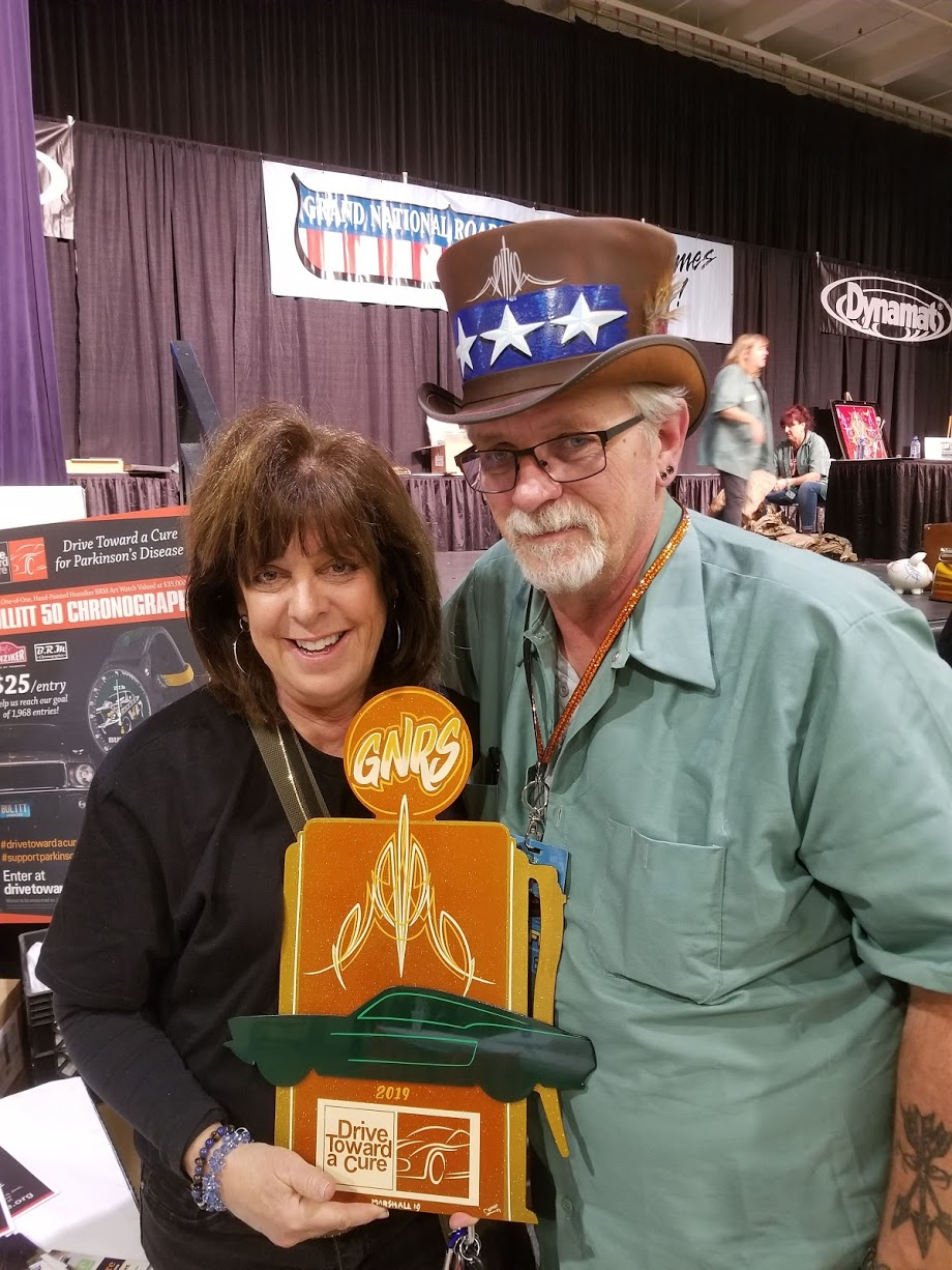 Deb Pollack, director of Drive Toward a Cure, poses with a pinstriping artist who created a custom Grand National Roadster Show
