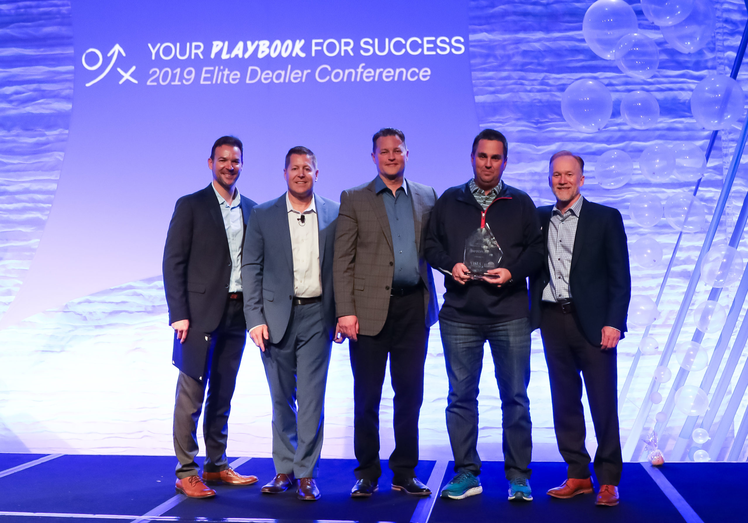 Josh Elliott (second from right), owner of Autoplex of Loveland, accepts the National Dealer of the Year award from Eastman Perf